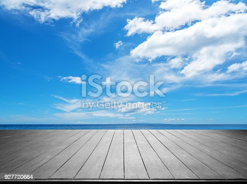 677933036 istock photo Wooden terrace with tropical ocean and blue sky background 927720664