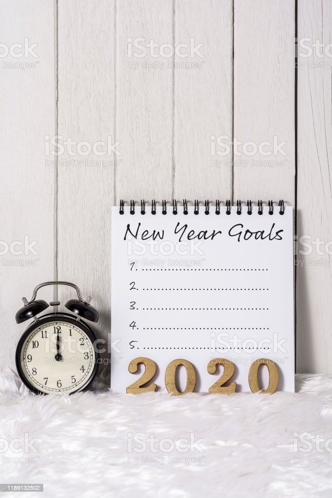 2020 wooden text and New Year\'s Goals List written on Notebook with...