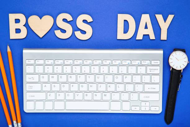 texto de madera boss day con lápices, reloj de pulsera y teclado sobre fondo azul - boss's day fotografías e imágenes de stock