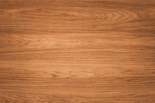 High quality brown wooden background. This background features a distinguished wood grain pattern complete with wavy lines. The colour of the wood appears darker near the left and right edges, but becomes lighter near the middle.