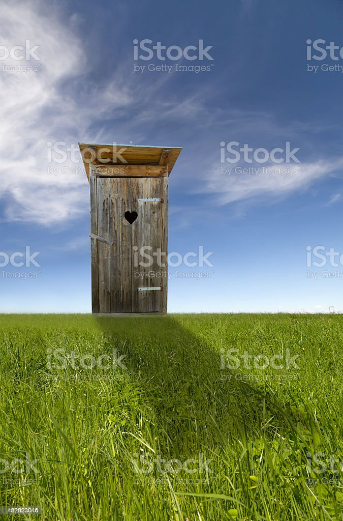 Wooden toilet, green field, blue sky stock photo