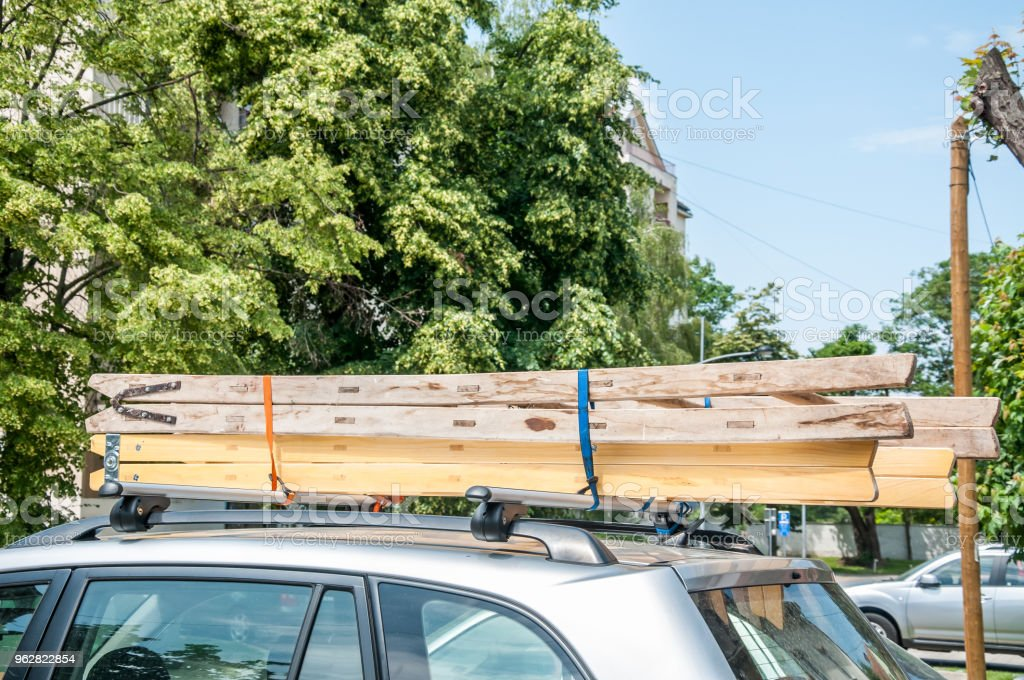 Wooden Tool Building Ladders Tied To The Roof Rack Of The