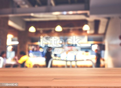 istock Wooden top table in front of abstract blurred background of restaurant lights. 1159449240