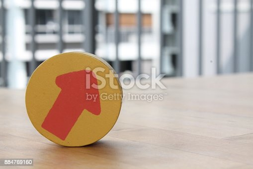 istock Wooden toy arrow on the circle on the table. 884769160