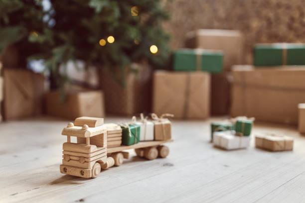 Hölzernes Spielzeugauto mit Weihnachts-Geschenk-Boxen an der Spitze. Selektiven Fokus auf Auto – Foto