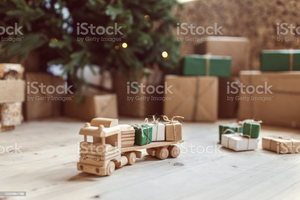 Wooden toy car with christmas gift boxes on top