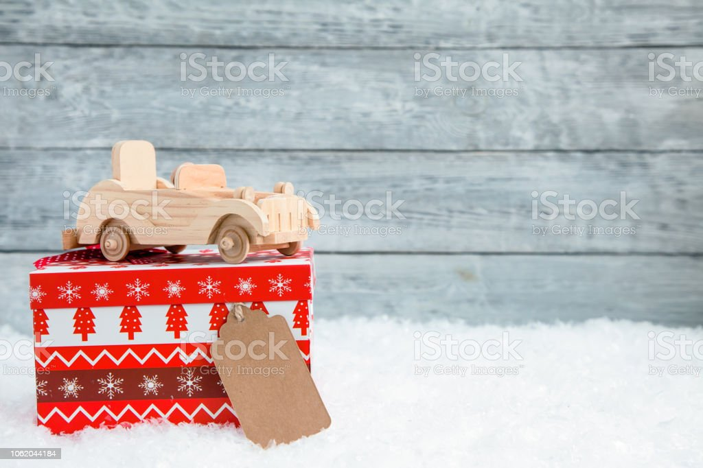 wooden toy car on Red Christmas box. Concept of Christmas or New Year