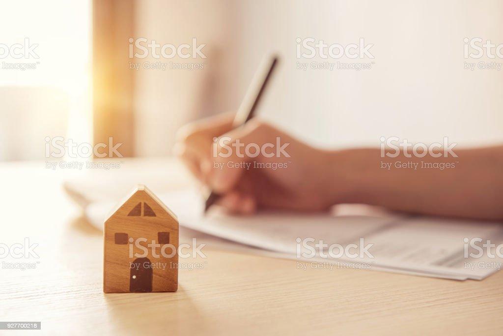 Holzspielzeug Haus mit Frau unterschreibt einen Kaufvertrag oder Hypotheken für Immobilien Wohnkonzept. – Foto