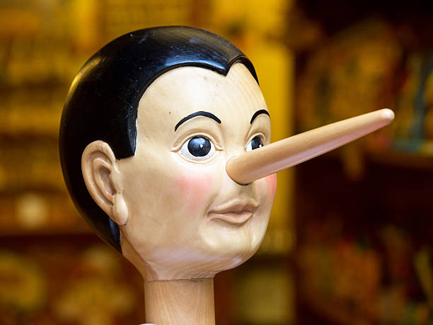 Wooden toy Pinocchio head with long nose on stick Wooden pinocchio doll with his long nose. ventriloquist's dummy stock pictures, royalty-free photos & images