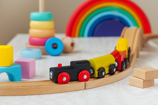 Wooden toys concept. Wooden toy railway and pyramid in the children room.