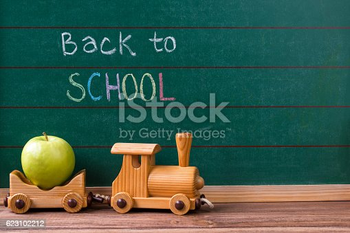 Wooden Toy Train Carrying A Green Apple On Chalkboard Background Stock Photo