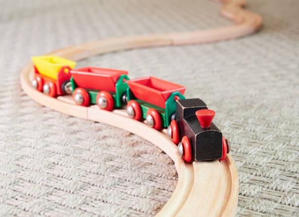 Wooden toy train running on miniature railroad stock photo