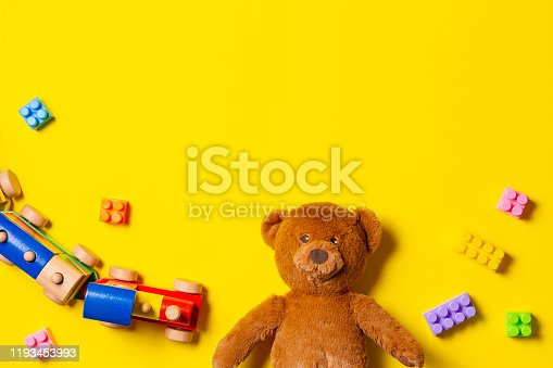 Baby kids toys background. Teddy bear, wooden train and colorful blocks on yellow background. Top viewBaby kids toys background. Teddy bear, wooden train and colorful blocks on yellow background. Top viewBaby kids toys background. Teddy bear, wooden train and colorful blocks on yellow background