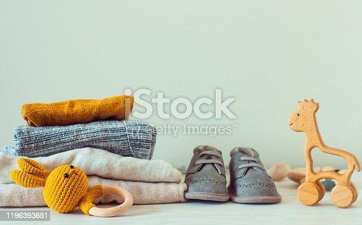 678651100 istock photo Wooden toys, baby shoes and organic clothes on the shelf 1196393651