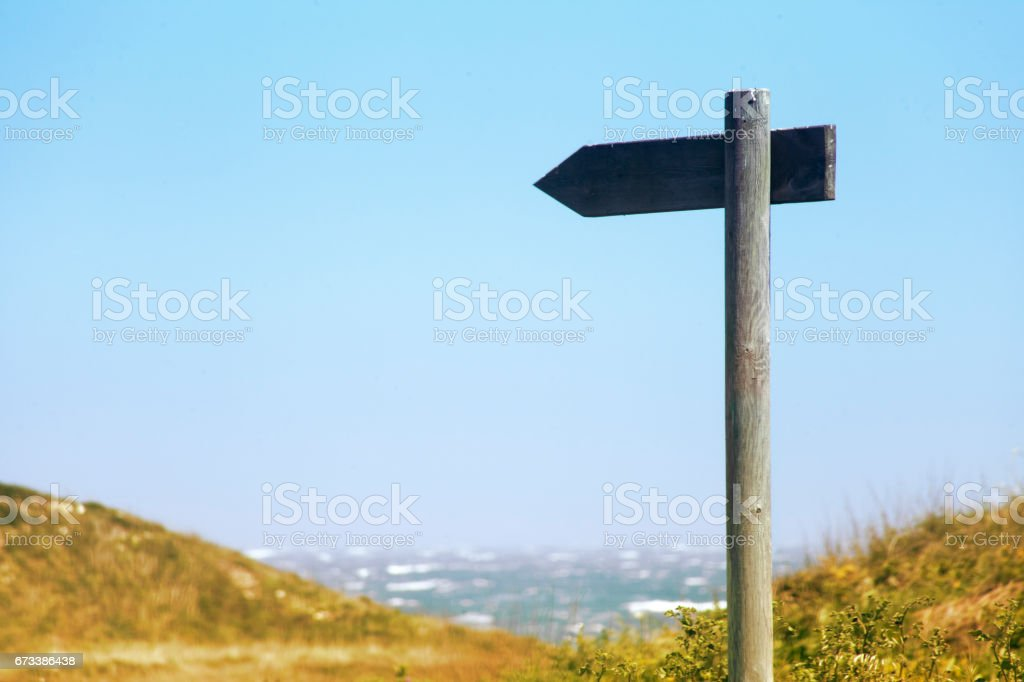 Wooden trail sign post with clear blue sky and seascape background. stock photo