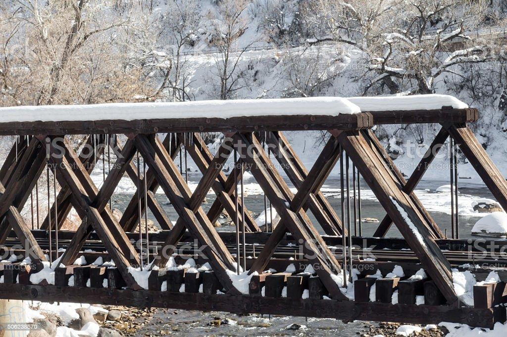 Wooden train bridge crossing the wintertime Animas river stock photo