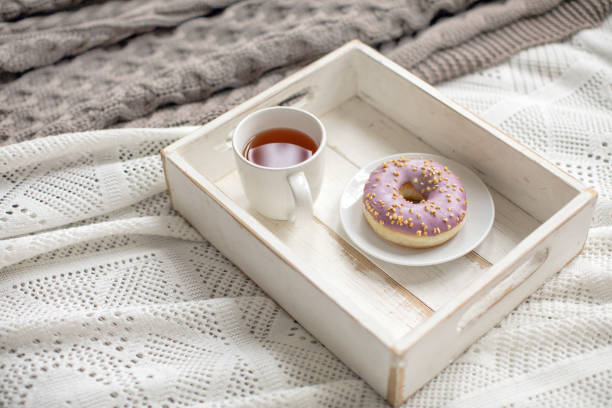 Wooden tray with tea and served doughnut stock photo