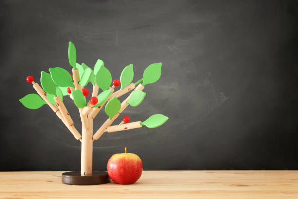 wooden tree puzzle over table and blackboard background stock photo