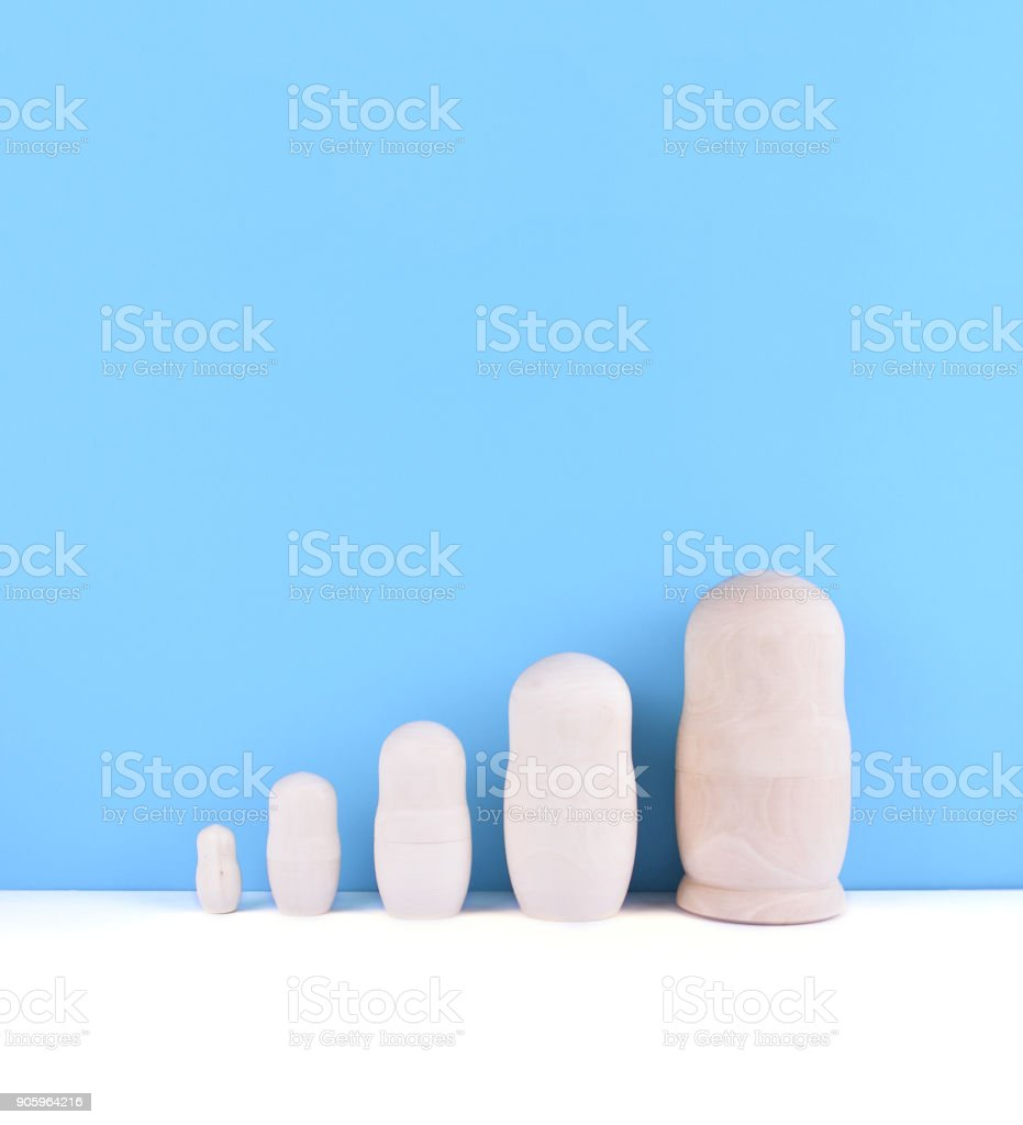 Wooden unpainted russian nested dolls. stock photo