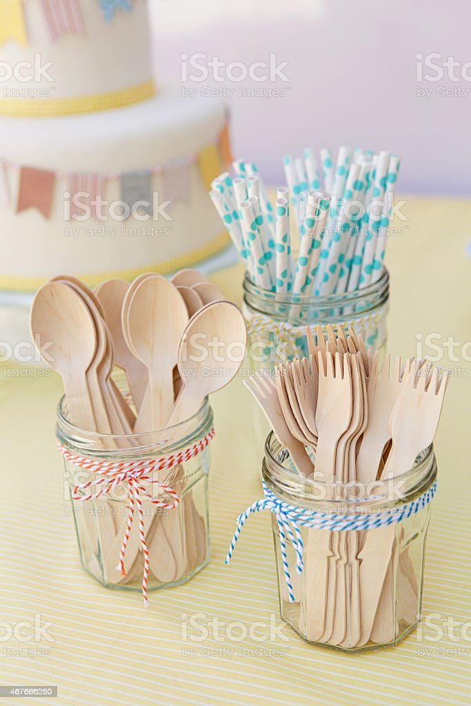 Wooden utensils and paper straws arranged on table top stock photo