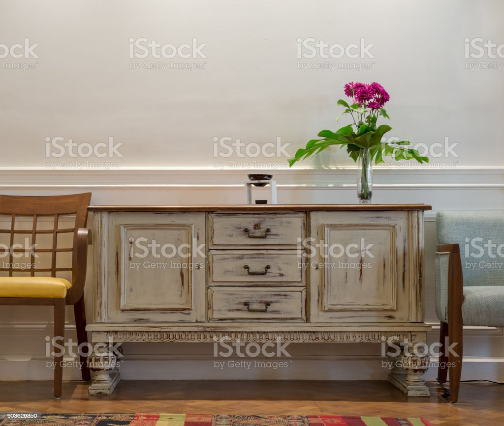 Wooden vintage off white sideboard, glass vase with red flowers, two chairs on white wall and wooden parquet floor stock photo
