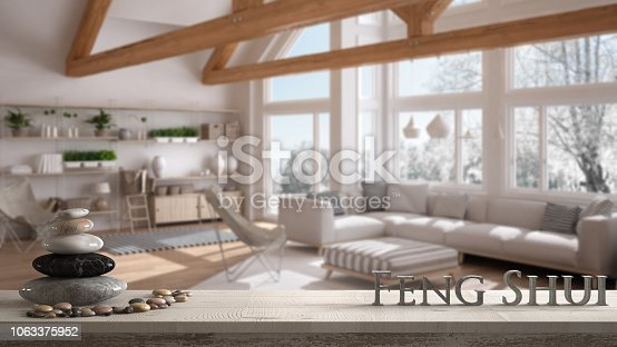 Wooden vintage table shelf with pebble balance and 3d letters making the word feng shui over blurred living room of eco house, wooden roof trusses, zen concept interior design