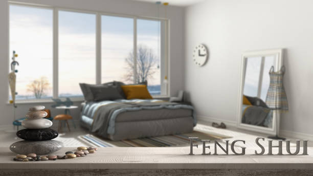 Wooden vintage table shelf with pebble balance and 3d letters making the word feng shui over blurred modern colored bedroom with big panoramic window, zen concept interior design stock photo