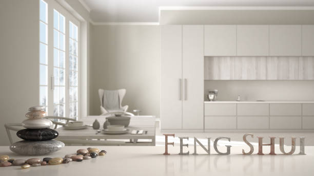 Wooden vintage table shelf with stone balance and 3d letters making the word feng shui over classic beige kitchen with dining table laid for two, zen concept interior design stock photo