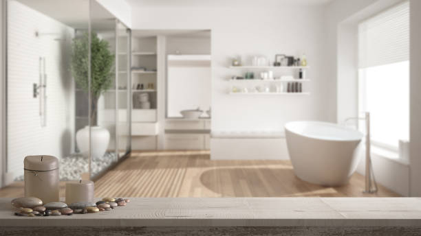 Wooden vintage table top or shelf with candles and pebbles, zen mood, over blurred minimalist bathroom with shower and walk-in closet, white architecture interior design stock photo