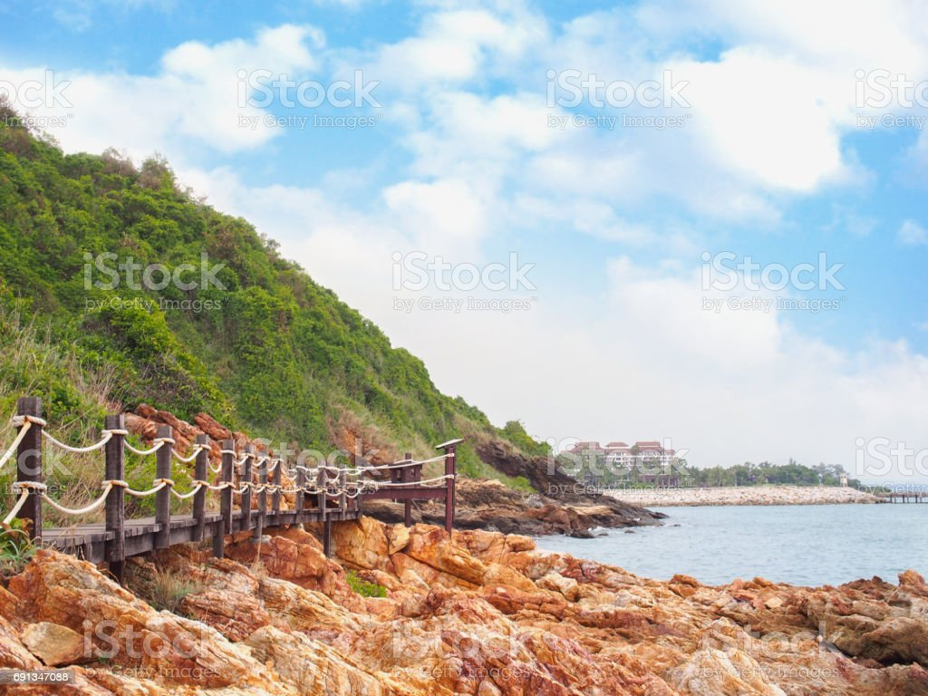 wooden walkway bridge with mountain landscape  against blue sky stock photo