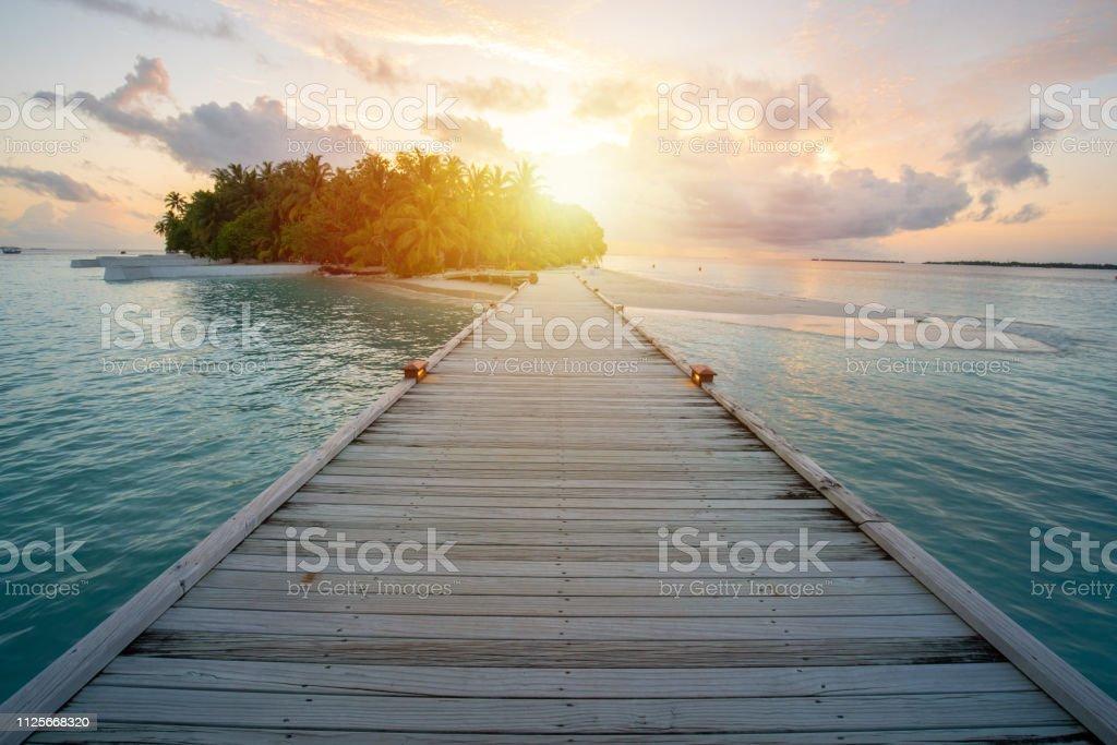 Holzsteg ins Resort in Malediven, Sonne Blendung von Sonnenuntergang – Foto