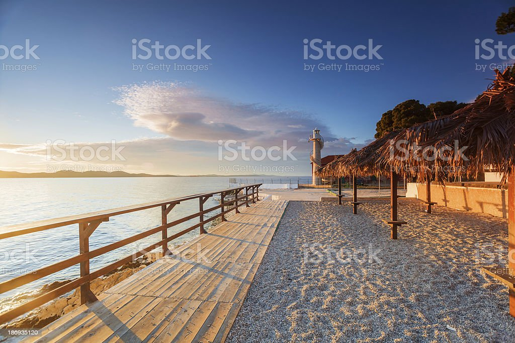 Wooden walkway leading to a lighthouse in Zadar, Croatia royalty-free stock photo
