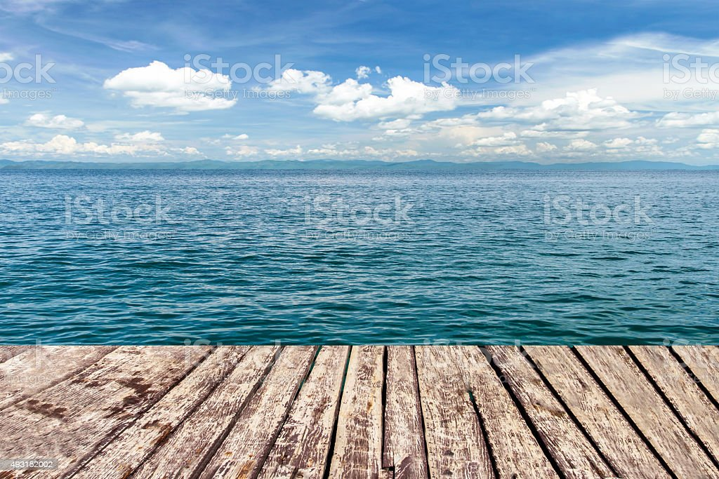 wooden walkway on sea and blue sky stock photo
