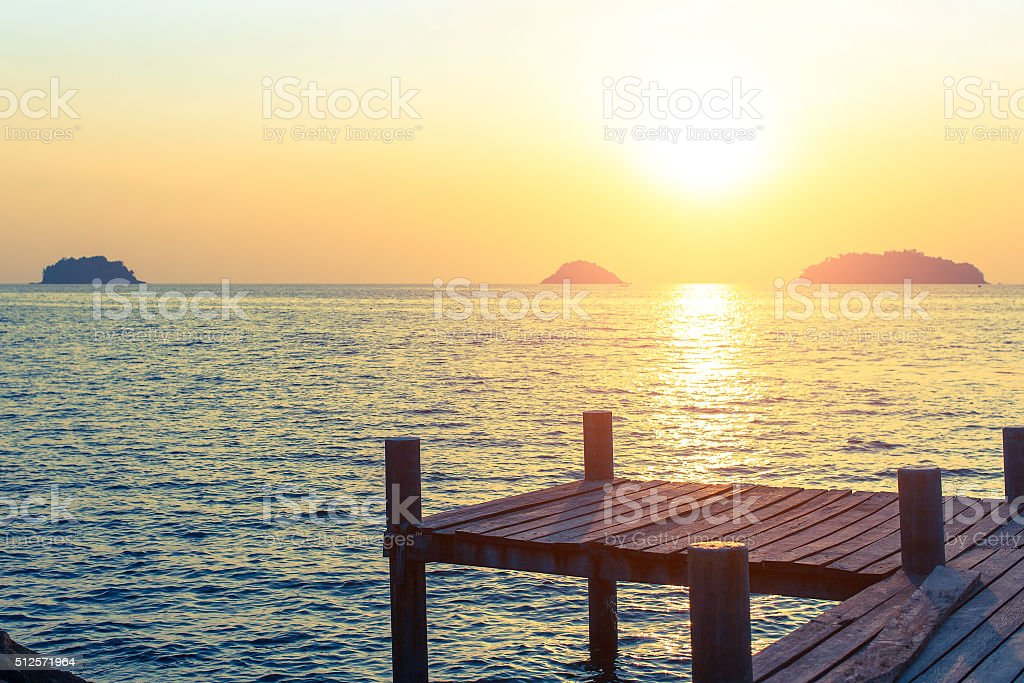 Wooden walkway on the sea coast during sunset. stock photo