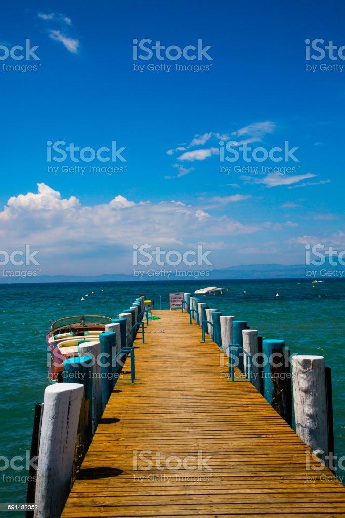 Wooden walkway on the shore of Bardolino, blue sky stock photo