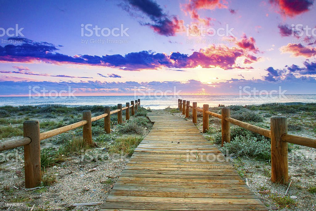 Wooden walkway through grass to beach under colorful sky stock photo