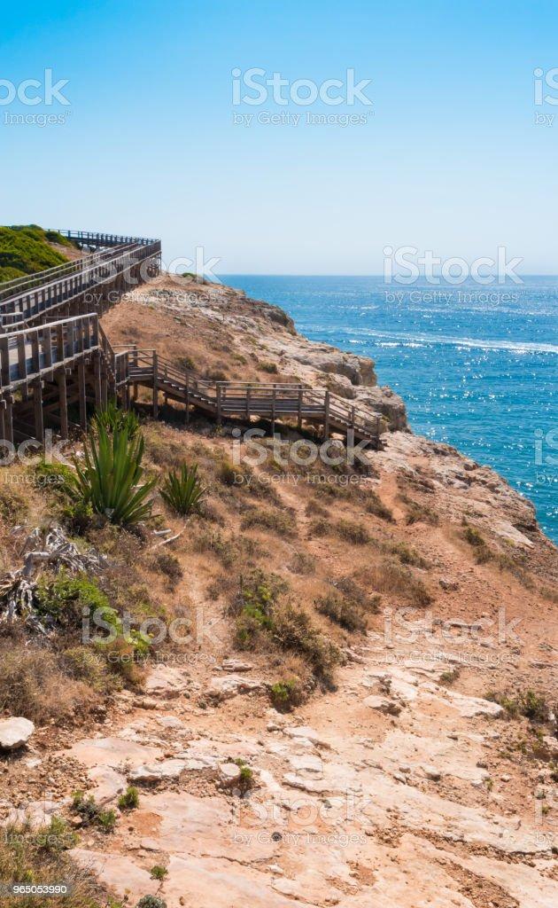 Wooden walkway to beautiful Carvoeiro beach with cliff and rock formation Algarve region Portugal zbiór zdjęć royalty-free