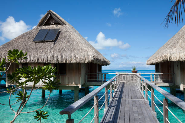 Wooden walkways over the water of the blue tropical sea to authentic traditional Polynesian thatched roof houses with eco-friendly use of solar panels. Polynesia, Tahiti