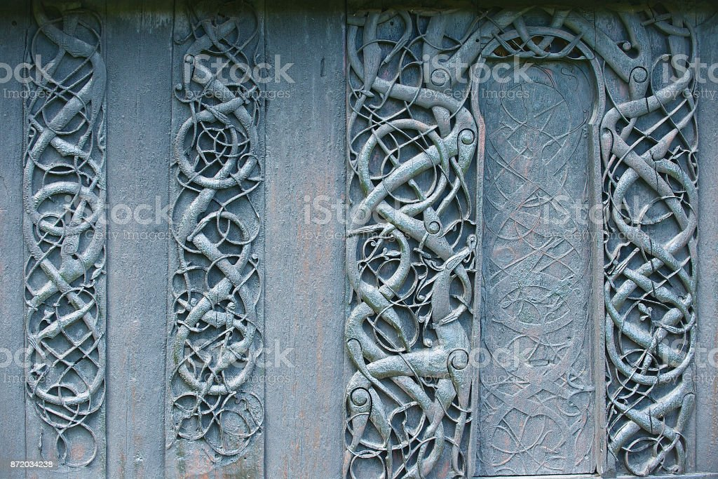 Wooden wall carved decoration of the medieval Urnes Stave church with viking motifs in Ornes, Norway. stock photo