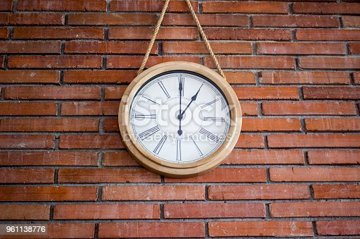 671883446istockphoto Wooden wall clock with roman numerals hanging in a red brick wall. 961138776