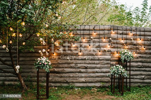 Wooden wall decorated garland with luminous bulbs and electric lamps decorated flowers. Original wedding floral decoration.  Wedding. Reception. Lounge zone.