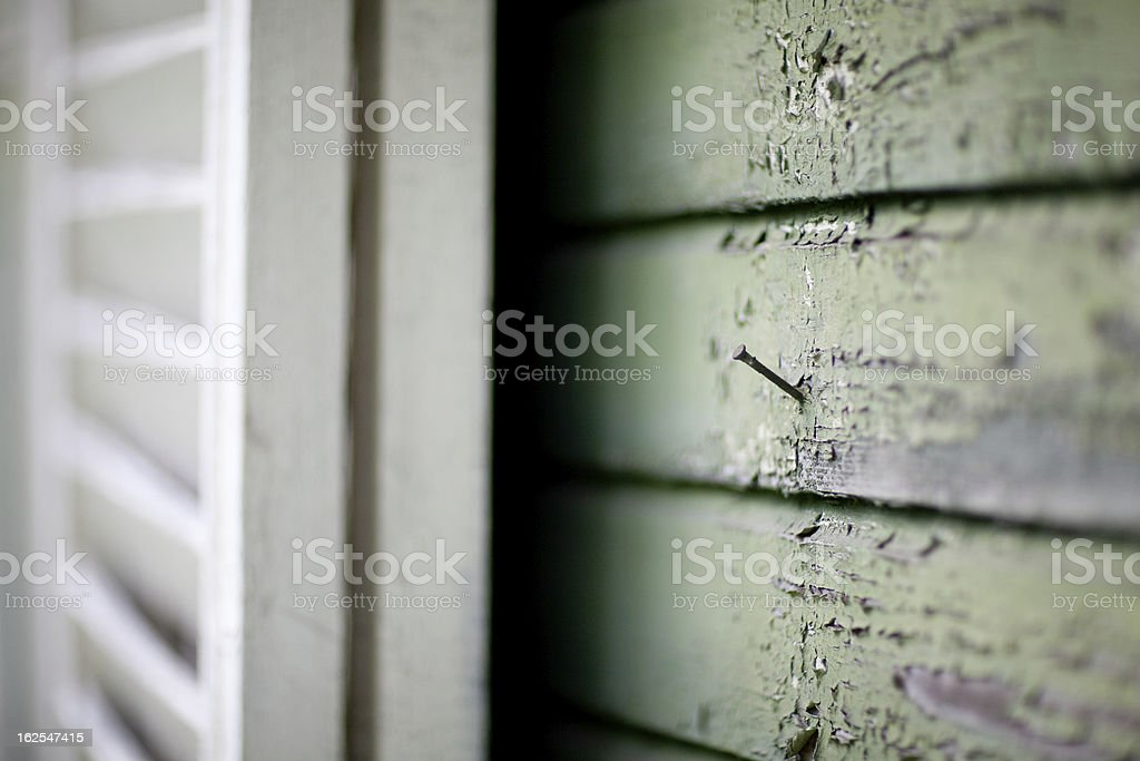 Wooden wall with peeling paint and rusty nail royalty-free stock photo