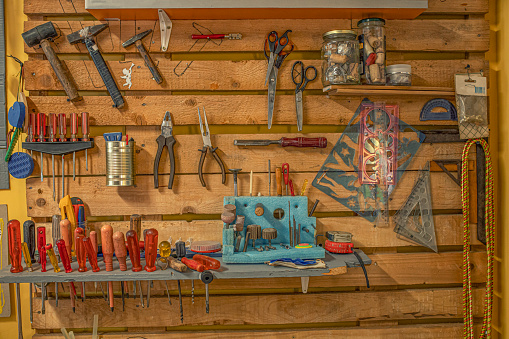 Wooden wall full of hammer, pliers, scissors and other tools. Creative workshop