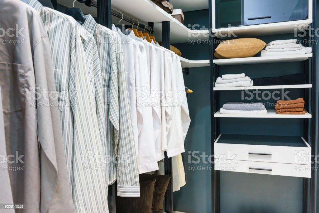 Holzschrank in begehbaren Kleiderschrank mit Klamotten auf der Schiene, Einrichtungskonzept – Foto