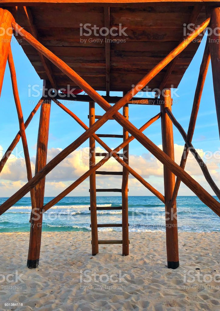 Wooden watchtower on the empty beach at sunset stock photo