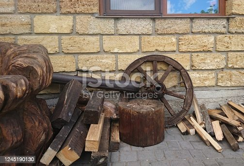 Wooden wheel and firewood on a brick wall background