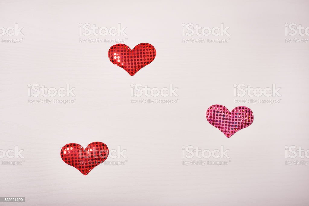 Wooden white background with a branch of pine and three hearts. stock photo