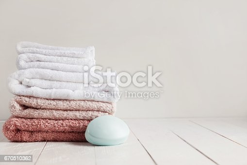 istock Wooden white table in the bathroom with a set of towels and scented soap 670510362