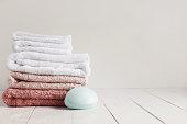 タオル、香料入りの石鹸のセットが付いている浴室の木製の白いテーブル