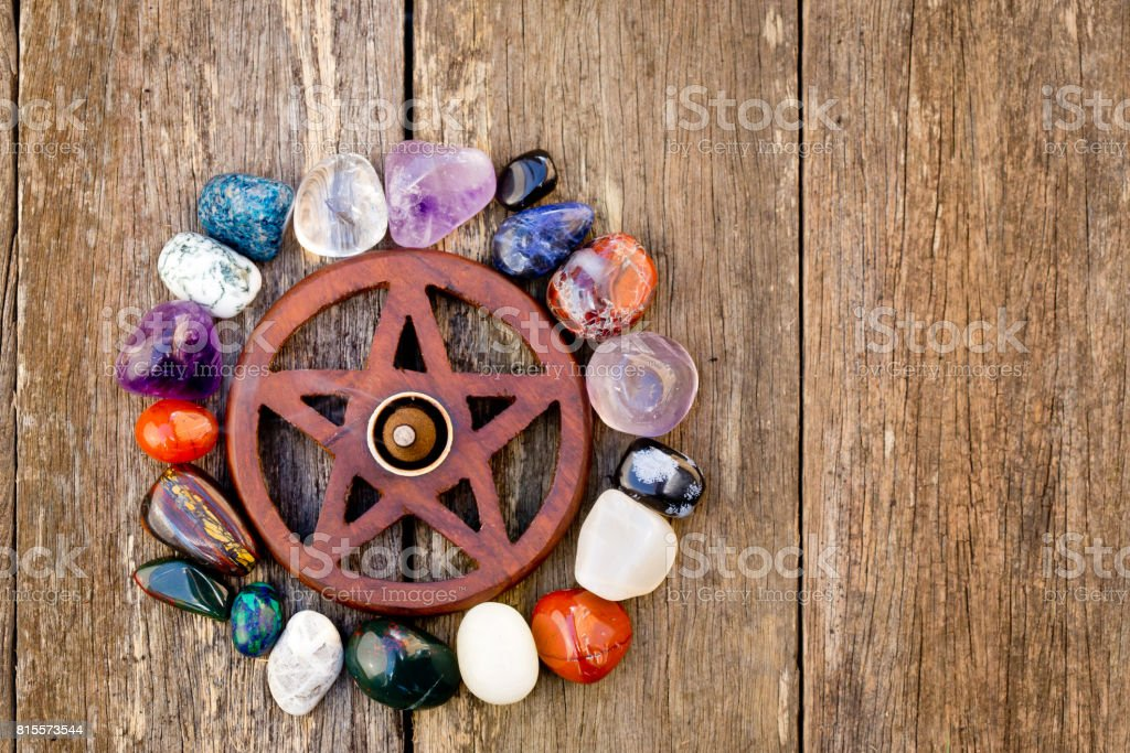 Wooden wiccan pentagram with incense burning surrounded by crystals - on wooden background stock photo